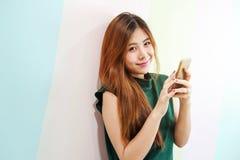 Stående av den unga kvinnan som ler, medan genom att använda den smarta telefonen på wen arkivbild
