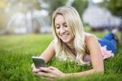 Stående av den unga kvinnan som ligger på en grön gräsmatta Royaltyfria Foton