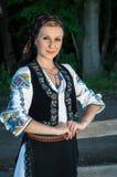Stående av den unga kvinnan som poserar yttersidan i rumänsk tra Arkivbilder