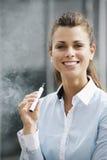 Stående av den unga kvinnan som röker av den utomhus- elektroniska cigaretten Arkivbild