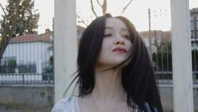 Stående av den unga kvinnan som rakt till ser från vänstert och bläddrar hår lager videofilmer