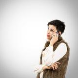 Stående av den unga kvinnan som talar på mobiltelefonen Arkivfoton