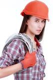 Stående av den unga kvinnliga byggmästaren i hjälm med cabel på vit Arkivbilder