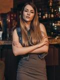 Stående av den unga kvinnliga modellen med ganska hår som lutar henne armbågar på stångräknaren som ser kameran i tappningrestaur arkivfoton