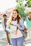 Stående av den unga kvinnliga studenten med vänner i bakgrund på gatan royaltyfri foto