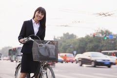 Stående av den unga le affärskvinnan som rider en cykel på gatan i Peking som ser kameran arkivfoto