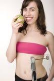 Stående av den unga le flickan med det gröna äpplet och våg royaltyfri foto
