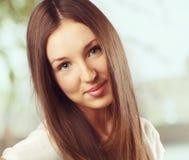 Stående av den unga le kvinnan med långa hår fotografering för bildbyråer