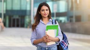 Stående av den unga le kvinnan som rymmer böcker, studie, utbildning, kunskap, målbegrepp fotografering för bildbyråer