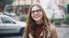 Stående av den unga le studenten i exponeringsglas som ser kameran och dricker te Lycklig kvinna som går i Paris, Frankrike stock video