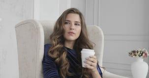 Stående av den unga ledsna brunhåriga kvinnan som dricker kaffe i morgonen arkivfilmer