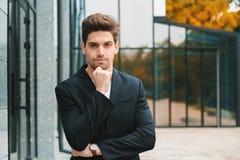 Stående av den unga lyckade eftertänksamma affärsmannen i stad Man i affärsomslag på kontorsbyggnadbakgrund stiligt royaltyfria bilder
