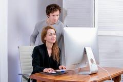 Stående av den unga lyckade kvinnan och mannen på kontoret De ser skärmen som gör kontorsarbete Black Friday eller Cyber måndag royaltyfria bilder