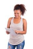 Stående av den unga lyckliga afrikanska kvinnan som använder den Digital minnestavlan Fotografering för Bildbyråer