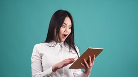 Stående av den unga lyckliga asiatiska kvinnan som använder den digitala minnestavlan lager videofilmer