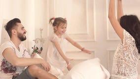 Stående av den unga lyckliga familjen som tillsammans spelar med kuddar i säng lager videofilmer