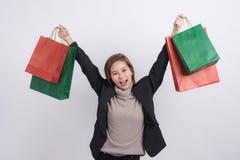 Stående av den unga lyckliga le asiatiska kvinnan med shoppingpåsar och hållande shoppingpåsar ovanför hennes huvud Arkivbilder