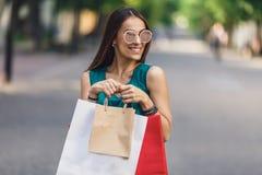 Stående av den unga lyckliga le kvinnan med shoppingpåsar som tycker om i shopping Positiv sinnesrörelser och shoppingdag royaltyfri bild