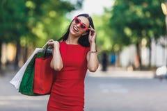 Stående av den unga lyckliga le kvinnan med shoppingpåsar som tycker om i shopping Positiv sinnesrörelser och shoppingdag fotografering för bildbyråer