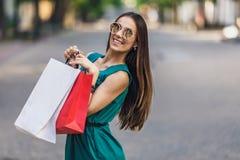 Stående av den unga lyckliga le kvinnan med shoppingpåsar som tycker om i shopping Positiv sinnesrörelser och shoppingdag royaltyfri fotografi