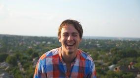 Stående av den unga lyckliga mannen som sitter på tak på cityscapebakgrund Stilig grabb som skrattar och visar glädjeuttryck stock video