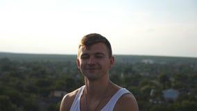 Stående av den unga lyckliga mannen som sitter på tak på cityscapebakgrund Stilig le grabb som ser in i kamera med arkivfilmer