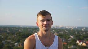 Stående av den unga lyckliga mannen som sitter på tak på cityscapebakgrund Stilig le grabb som ser in i kamera med stock video