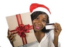 Stående av den unga lyckliga och härliga svarta afrikansk amerikankvinnan i den Santa Claus hatten som rymmer den närvarande aske royaltyfria foton