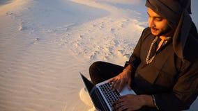 Stående av den unga manliga muslimska studenten, som skrivar ut på datortangentbordet och kopplar av som sitter på sand bland san lager videofilmer