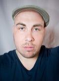 Stående av den unga mannen i ett lock fotografering för bildbyråer