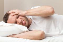 Stående av den unga mannen i säng med huvudvärk royaltyfri bild