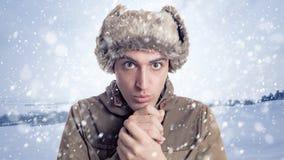 Stående av den unga mannen med eskimo hatt- och vinterbakgrund royaltyfri bild