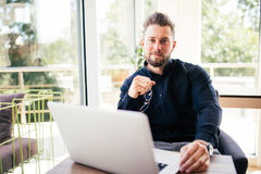 Stående av den unga mannen med exponeringsglas i händer som sitter på hans skrivbord i kontoret Royaltyfri Foto