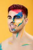 Stående av den unga mannen med kulör framsidamålarfärg på gul bakgrund Yrkesmässigt makeupmode Fantasikonstmakeup Royaltyfria Foton