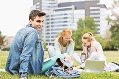 Stående av den unga mannen med kvinnliga vänner som studerar på universitetsområde arkivfoto