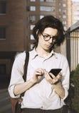 Stående av den unga mannen med smartphonen på cityscapebakgrund, frilans- arbetare Royaltyfri Bild