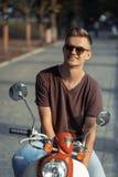 Stående av den unga mannen på mopeden Royaltyfria Foton