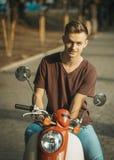 Stående av den unga mannen på mopeden Arkivbild