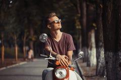 Stående av den unga mannen på mopeden Royaltyfri Fotografi