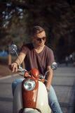 Stående av den unga mannen på mopeden Royaltyfri Foto