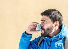 Stående av den unga mannen som använder astmainhalatorn royaltyfri foto