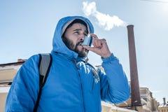 Stående av den unga mannen som använder den utomhus- astmainhalatorn royaltyfri foto