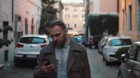 Stående av den unga mannen som går i aftonstaden med smartphonen Stiligt manligt smsa med pekskärmen långsam rörelse lager videofilmer