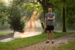 Stående av den unga mannen som gör spring för utomhus- aktivitet Arkivfoto