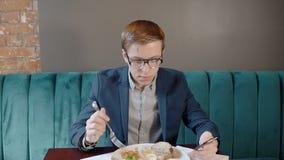 Stående av den unga mannen som ser till hans smartphone, medan ha frukosten i kafé arkivfilmer