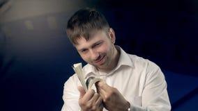 Stående av den unga mannen som visar mycket pengar till kameran och är egentligen glad om den arkivfilmer