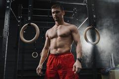 Stående av den unga muskulösa crossfitidrottsman nen som förbereder sig för genomkörare på idrottshallen