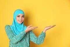Stående av den unga muslimska kvinnan i hijab mot färgbakgrund royaltyfri foto