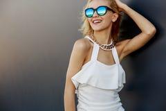Stående av den unga nätta blonda modellen i stilfull solglasögon för kall spegel royaltyfri foto