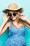 Stående av den unga nätta kvinnan i sommarhatt och solglasögon på blå bakgrund arkivbild